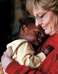 "Independent/Barrett Stinson  ""It's great watching her come alive,"" said Jane Qualset, right, who holds her adopted daughter Rumbidzai ""Rubi"" Qualset.  ""It's been a real spiritual journey for us.""  The Qualset's are believed to be the first white couple from a foreign country to be granted custody for a black child from Zimbabwe."