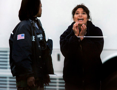 An unidentified prisoner (right) yells to onlookers as she is escorted to a waiting bus Tuesday morning during an Immigration and Customs Enforcement raid at the Swift & Co. plant in Grand Island.