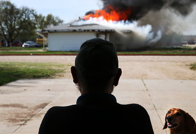 With his dog, Rosie, beside him, neighbor Henry Polak watches Tuesday morning as Grand Island Fire Department personnel burn a house down across the street from his home to perform training exercises at 1604 Raymond Drive. (Independent/Barrett Stinson)