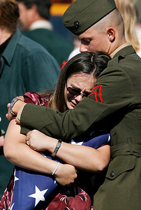Marine Pfc. Kevin Godfrey (right) comforts his sister, Karen Pfeifer, after the graveside ceremony for her husband, Pfc. Christopher Pfeifer, Wednesday afternoon at St. Michael's Cemetery south of Spalding. Pfeifer died Sept. 25 of injuries he suffered in August when insurgents attacked his unit in Afghanistan.