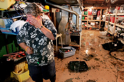 "Standing in 6-and-a-half inches of water in her basement, Cyndie Larson wipes a tear from her eyes while describing the groundwater-related flooding problems she's had in her home of 20 years since April 24. ""It's been as high as 16 inches. It's 6-and-a-half today,"" said Larson."