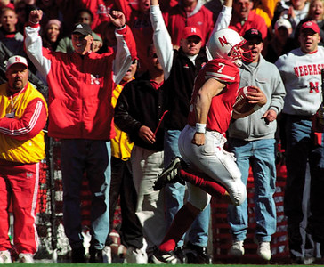 "Independent/Barrett Stinson  On his way to score after catching a pass during a fourth quarter trick play, Husker quarterback Eric Crouch is urged on by two former Huskers involved in another ""catch"" Husker fans might remember, Scott Frost (second from left) and Matt Davison (center).  The Huskers defeated Oklahoma 20-10."