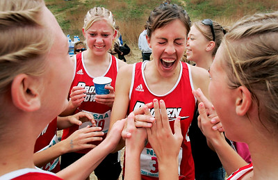 After claiming her second girls Class C cross country title in a row, Katelyn White (second from right) celebrates with her teammates, including Taylor Johnson (second from left), after hearing that their team placed second Friday during state cross country in Kearney.