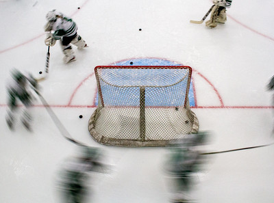 Holy Family Girls Hockey players skate behind the net during warmups.