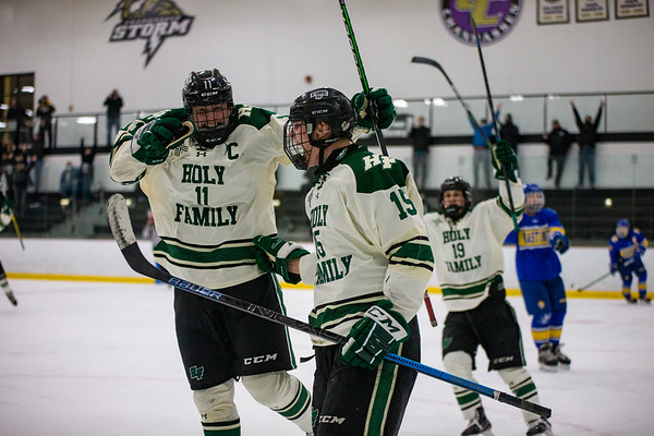 Luke Roelofs (left) and Marc Lund (right) celebrate scoring a goal in overtime to win the game.