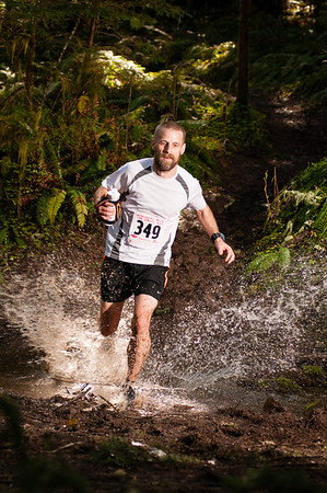 Cross Country runner Brian O'Connor splashes through a creek crossing at Run Wild Adventures Monunment Peak trail run outside Gates, Oregon.