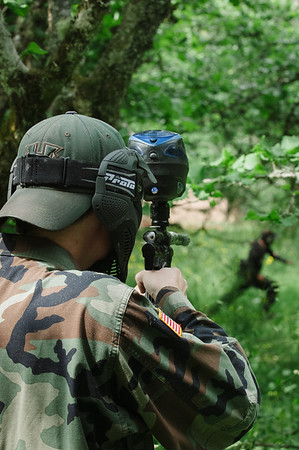 A paintball player has his marker ready as a member from the other team sprints for cover.