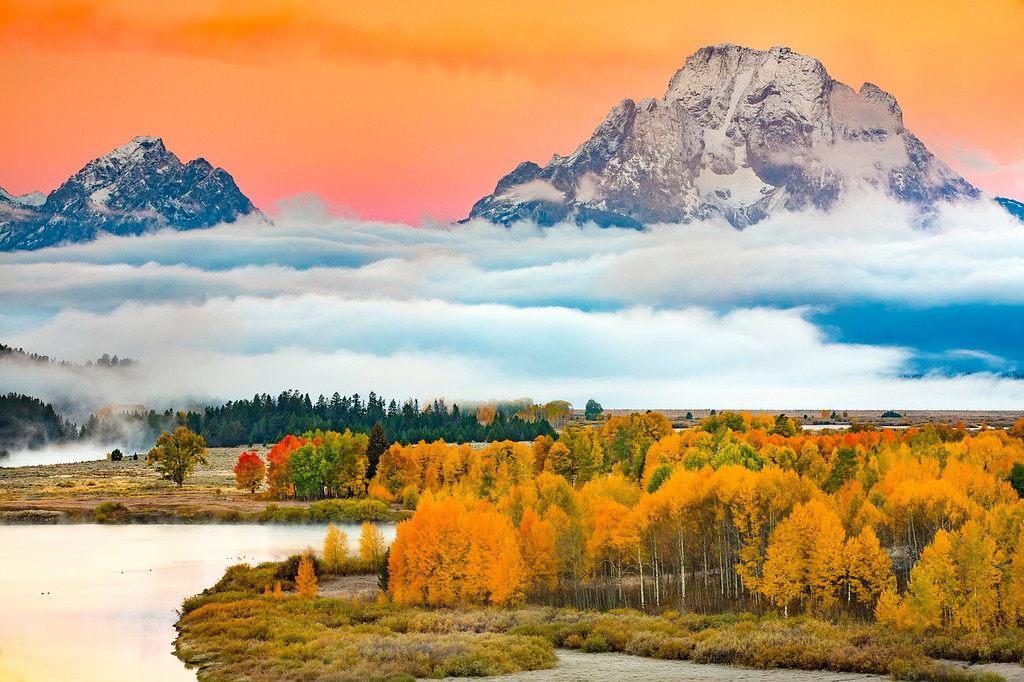 A fall sunrise at the infamous Oxbox Bend in Grand Teton National Park. The peaks of the Teton Range rise above the Snake River that meanders past golden canopies of cottonwoods and aspens just below Jackson Lake.