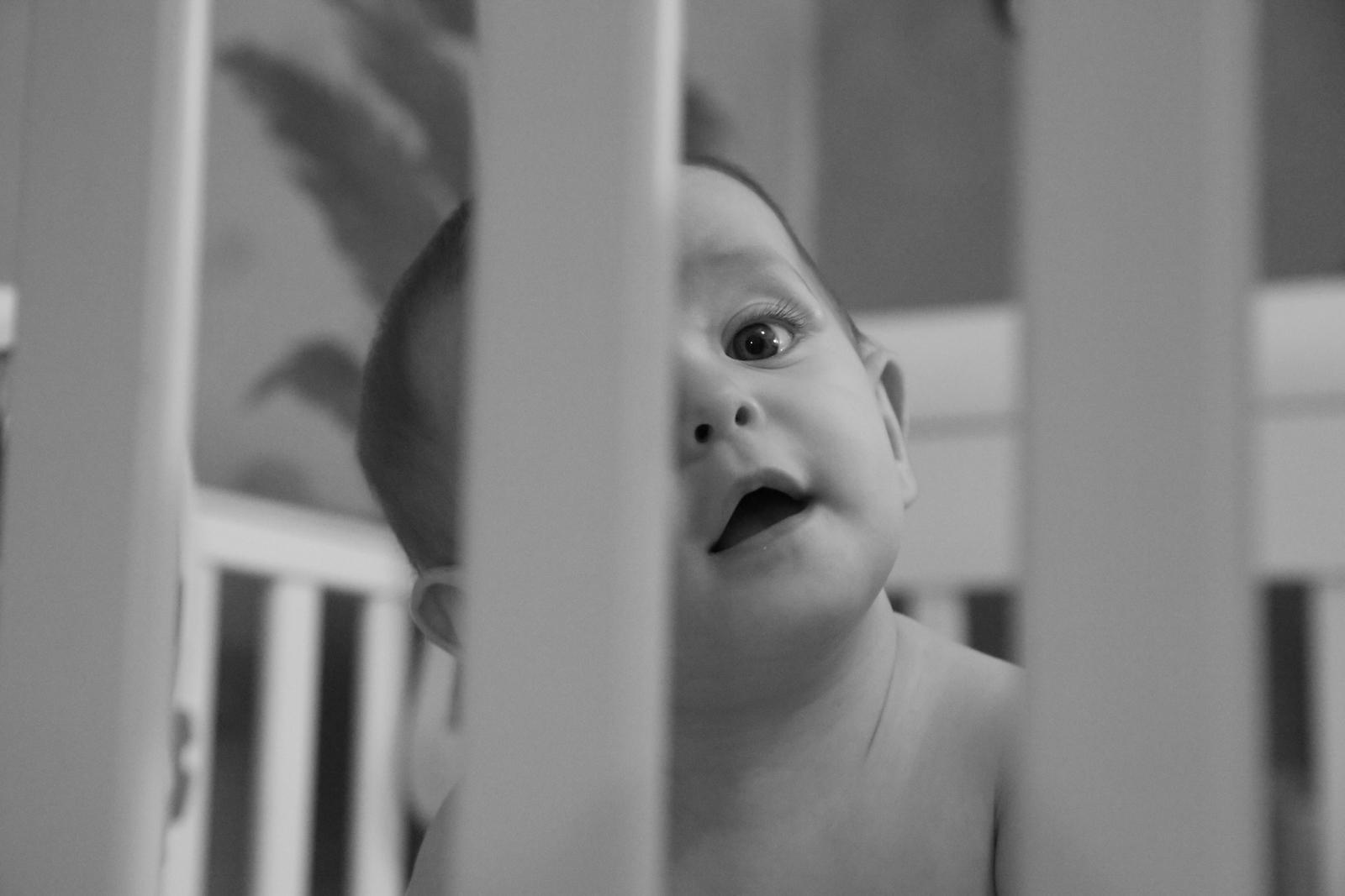 Baby peeking through her crib.