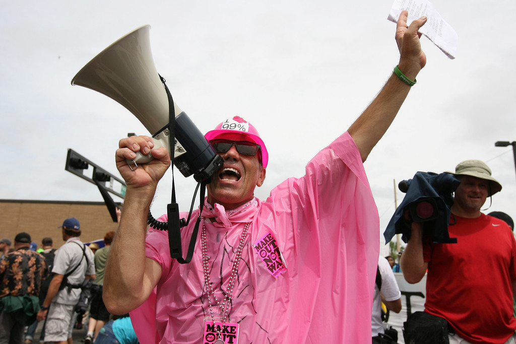 """A member of the Code Pink activist group shouts into a megaphone as the Coalition March on the RNC marches its way to the Republican National Convention """"public viewing area"""" in downtown Tampa, Florida.  Several groups were involved in the march, including Code Pink, Occupy Wall Street, and Food Not Bombs.  August 27th, 2012."""