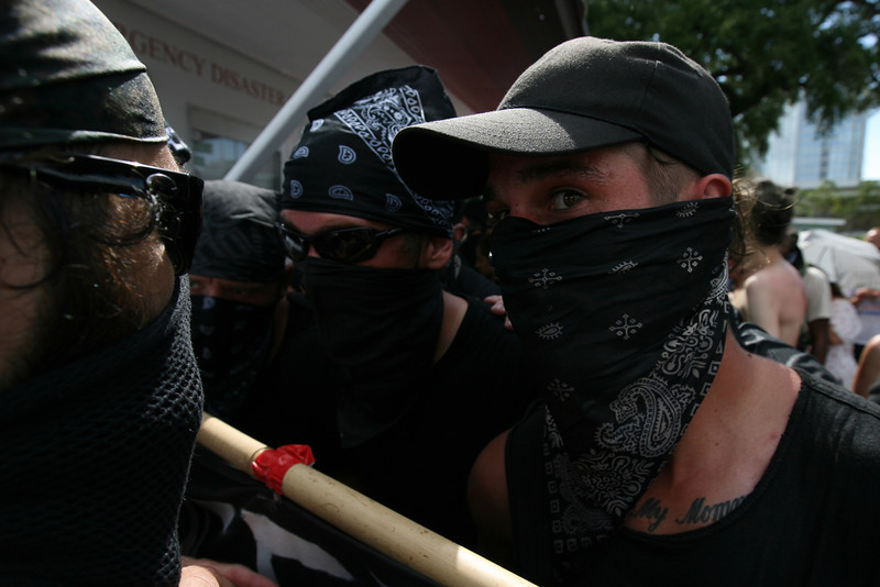 "Members of the black bloc discuss their plans to move forward into the ""public viewing area"" at the Republican National Convention where members of Westboro Baptist Church were currently protesting.  August 28th, 2012.  Tampa, Florida."