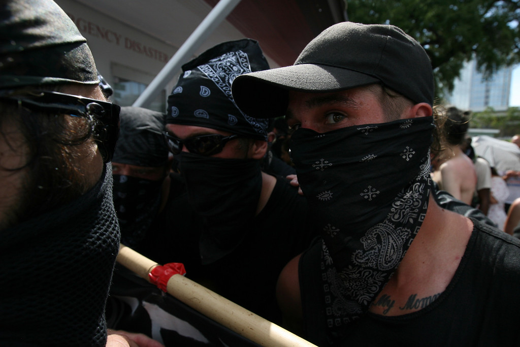 """Members of the black bloc discuss their plans to move forward into the """"public viewing area"""" at the Republican National Convention where members of Westboro Baptist Church were currently protesting.  August 28th, 2012.  Tampa, Florida."""