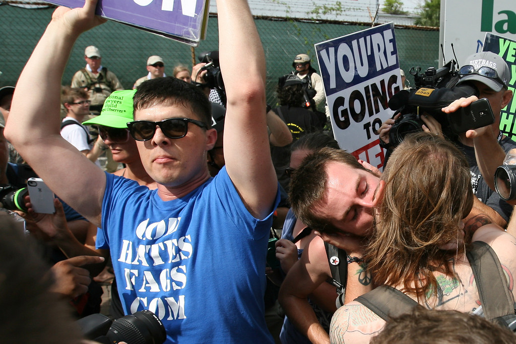 Two men kiss next to Westboro Baptist Church protesters in the public viewing area near Tampa Bay Times Forum where the 2012 Republican National Convention was held.  August 28th, 2012.  Tampa, Florida.