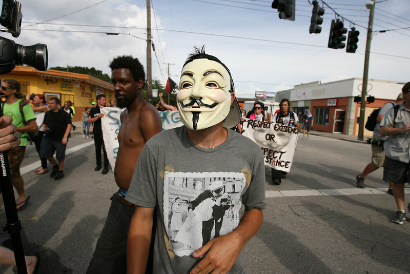 A man wearing a Guy Fawkes mask, the trademark accessory for supporters of the activist group Anonymous, approaches the Occupy encampment after a march through West Tampa.  August 29th, 2012.  Tampa, Florida.