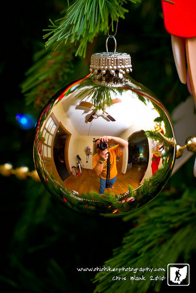Glass ball hanging on Christmas Tree equals quick self portrait.