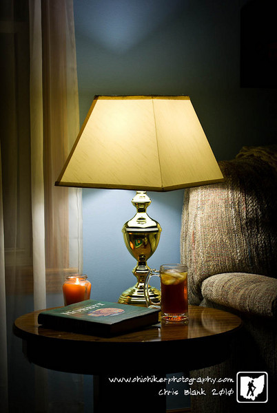 This end table sits in our front room by one of our couchs.  The light is on  timer and is one every night. The book has been sitting there for a year. I added the iced tea and candle to round out the photograph.