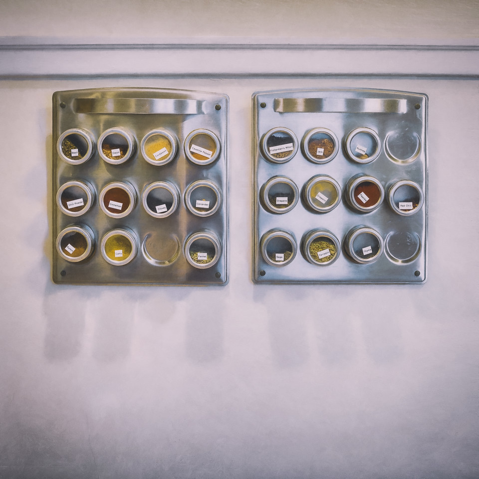 The kitchen spice racks that hang on the wall next to our stove.