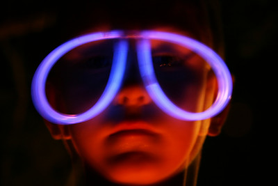 While camping with my sons Tiger Scout troop, I noticed that many of the young men had glowing glasses.  I asked this one to stand still while I hand held my camera.  He also held a red glow stick below his chin.  ...an interesting result.
