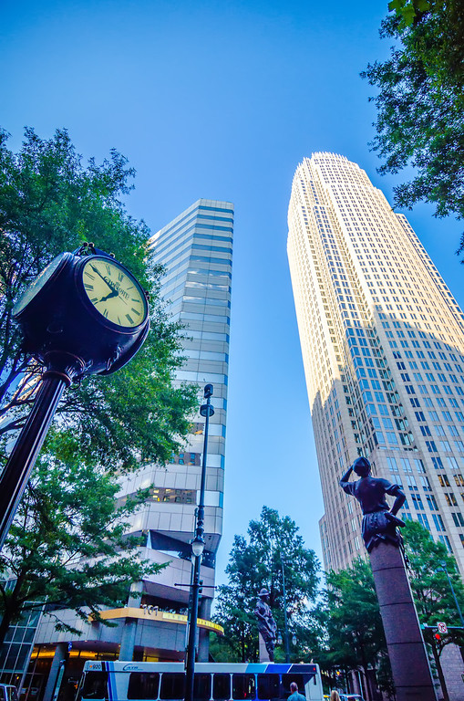 standing by the clock on city intersection at charlotte downtown