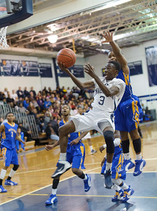 Derrick Akuoko, a Magruder guard goes for a reverse layup.