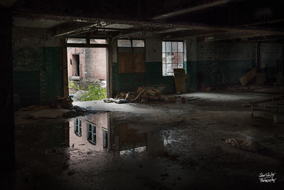 Outside building reflects on inside water.  © John Schiller Photography