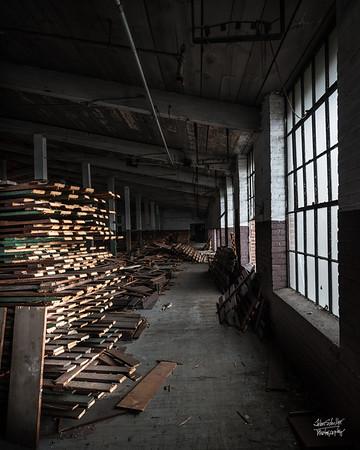 Storage rack wood piled high inthe dark corner of a storage room.  © John Schiller Photography