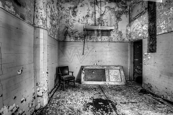 B&W of small office with leather chair and broken door.  © John Schiller Photography