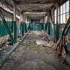 An freight elevator guards the end of a long, desolate corridor.<br /> <br /> © John Schiller Photography