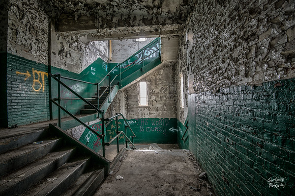 Light filters through the windows into green and white graffiti-decorated stairwells.   Peeling paint adds to the texture of the brick walls.  © John Schiller Photography