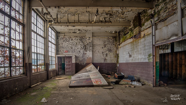 High window brighten the deteriorating interior walls of these former offices.  Green mold coats part of the floor.  © John Schiller Photography