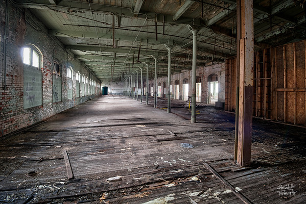 One of many large, open rooms with deteriorating wooden floors   © John Schiller Photography