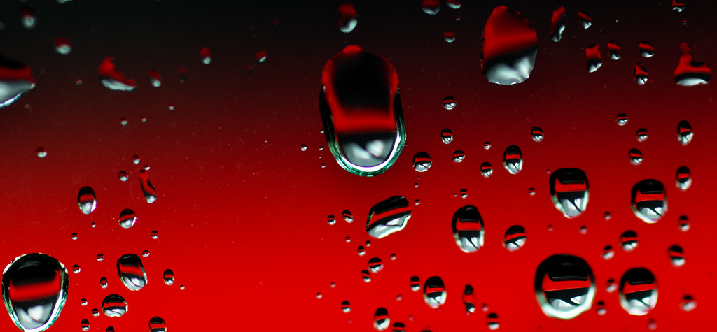 Rain drops on a car window...color is from the red car parked next to us. Picture taken in Maui Hawaii
