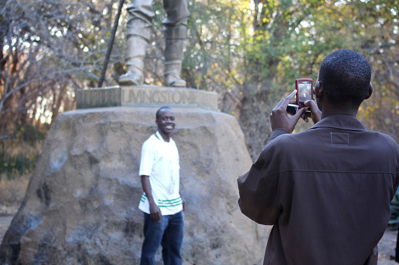 Man posing in front of the statue of Livingstone, Victoria Falls, Zimababwe (2011) © Copyrights Michel Botman Photography