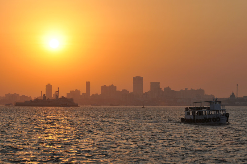 Mumbai coast line with the setting Sun. The Elephanta Caves are located just off Mumbai harbour in the Gharapuri Island also called Elephanta Island - a name given by the Portuguese when they ruled over this area. In 1987, the caves were designated a UNESCO World Heritage Site. Hewn out of solid rock, the Elephanta Caves date back to 600 AD. The caves attract many visitors who take an hour long ferry boat ride to reach from Gateway of India. The cave complex is a collection of rock-cut architecture with stone sculptures of Hindu Gods and Goddesses.