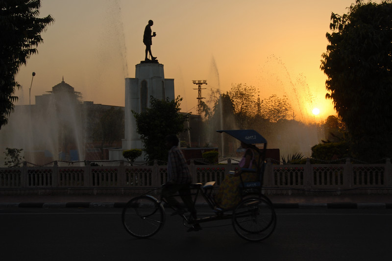 Sunset in Jaipur. Rajasthan with the silhoutte of Mahatma Gandhi's statue and a lady taking a ride in a human driven cycle rickshaw.