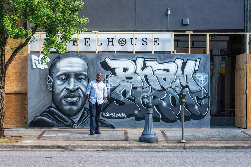 A man poses in front of the mural memorial for George Floyd