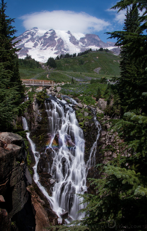 Myrtle Falls adorning the Majestic Mt Rainier One weekend - 2.5 days, 500 miles of drive, 5 miles of hiking, one national park, camping in the woods, sleeping under the stars, one broken car charger, one dead mobile by end of 1st day, one dead camera by 2nd - a memorable visit to Mt. Rainier National Park. As I'm going thru and processing the images, wanted to share a happy summer shot from the trip.   This week is a classical view of Mt Rainier along with Myrtle falls, from the heart of paradise area. My initial plans was to reach the spot for sunrise which did not work out. Actually it was so overcast and misty that the visibility was literally less than 2 feet during the early morning. By the time I reached the trail head it was around noon and the sun had decided to smile. I was glad to have hiked up to this sweet spot. The scattered clouds helped diffuse the light well enough to capture the moment – with the silky flow and even a small rainbow. The processing on this RAW shot was minimal (Lightroom) - decreased a bit of exposure, increased clarity and added a little vignette to focus on the falls. Feel free to share with the links below if u like the shot :)  Incase you are interested with the details (not sure how many would be!) Camera : Canon 7D Lens : Tamron 18-270mm Filter : Circular Polarizer + 3 stop Neutral Density Filter ISO 100 : 18 mm : f22 : 0.3 sec