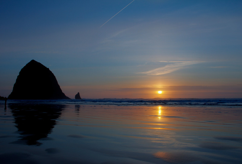This is a beautiful Cannon Beach sunset, on a cold winter evening. Haystack Rock @ Cannon Beach, is definitely an iconic location of the Oregon Coast. It is huge, i mean literally, standing at 235 feet tall. Makes one feel so small and humble ! We had planned for the tide pools at the rock, to get some hand on playing with Nemo's friends. Unfortunately, it was high tide and there was no way to get to the rock. Note to self : Next time check the tide table before going to the beach. Did u know, there is an app for that too :)   Anyways, the high tide did help is capturing a wonderful sunset. Loved the way how the cool blue of the sky and the golden sun, serenely reflects on the receding waters. Come join me for a evening walk and enjoy the sunset !!!