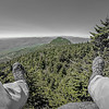 Hiker legs and boots view on the mountain peak relaxing outdoor mountain sport