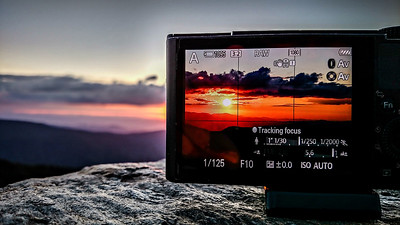 taking sunset photo with a camera in the mountains