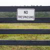 No trespassing sign against backdrop of farmland