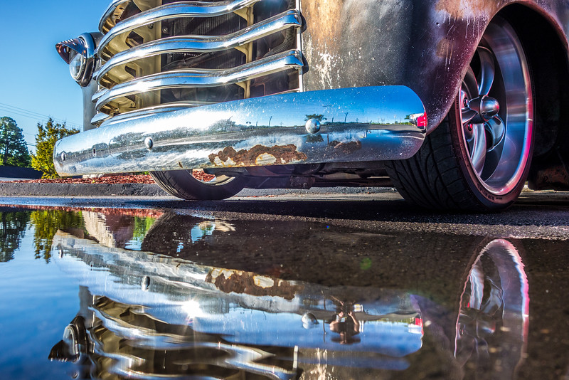 pick up truck and its grille reflecting in puddle
