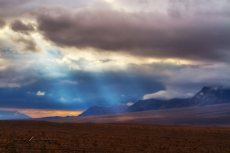 After the rain...<br /> The sun breaks through thick clouds to illuminate the eastern slopes of Tucki Mountain in central Death Valley National Park.  From Highway 190 across Devils Cornfield.