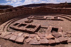 This large kiva has wall niches above a raised bench at the base of the room, a raised fire box, raised floor vaults, and four pits for the upright wooden posts to support the roof.