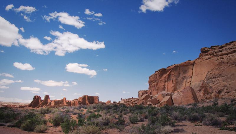 The ruins of Bonito Pueblo at the base of steep Chaco Canyon cliffs.