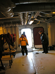 some of the team stepping out to climb down into a zodiac to get across to land