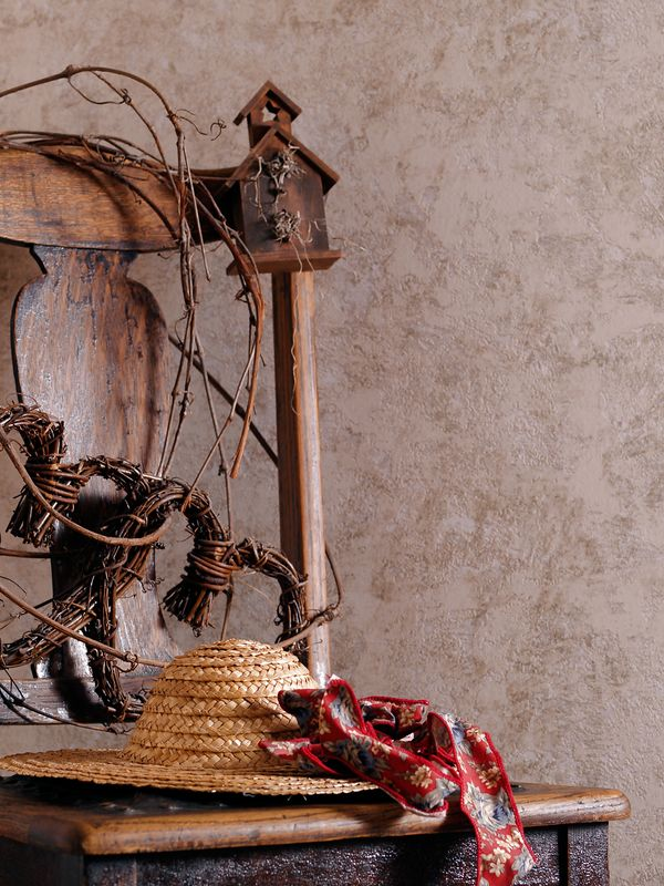 Antique chair decorated with a birdhouse, straw hat, and dried twigs.