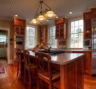 The beautiful, useful and spacious kitchen with a kitchen island gas stove, elegant cabinetry and fabulous light.