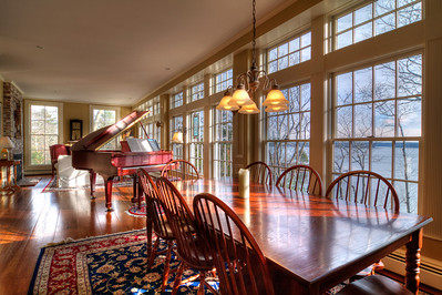 The beautiful dining room/living area, complete with baby grand piano and 40+ foot bank of floor to ceiling windows looking out on the Atlantic Ocean with views of Boothbay Harbor.