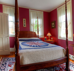 View of the elaborately carved four-poster bed in the burgundy bedroom.